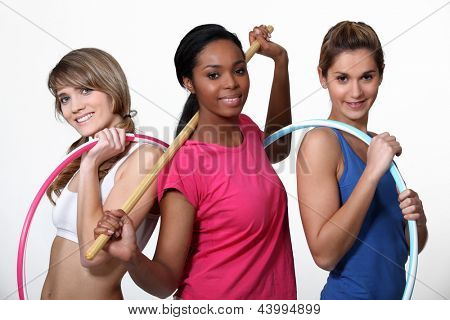 Three women limbering up at the gym