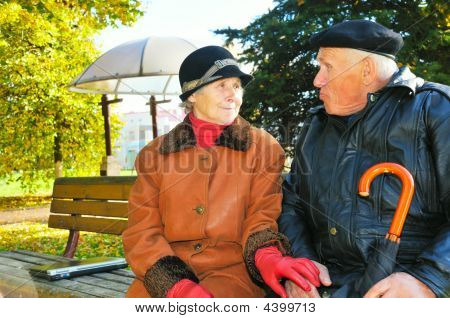 Pair Senior Sit On Bench