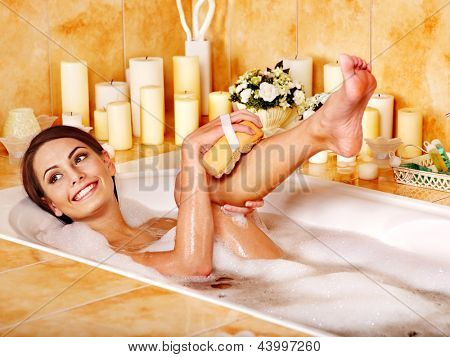 Young woman wash leg in bathtube.