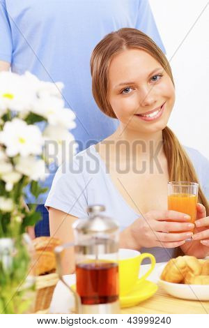 Young happy woman smiling and drinking juice