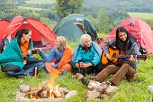 stock photo of tent  - Girls on vacation camping with tents listening girl playing guitar - JPG