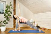 An image of a pretty woman doing yoga at home - Utthita Trikonasana