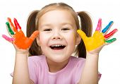 stock photo of messy  - Portrait of a cute cheerful girl showing her hands painted in bright colors - JPG