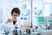 stock photo of flask  - Young male researcher carrying out scientific research in a lab  - JPG