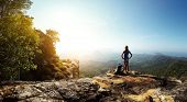 picture of wild adventure  - Hiker with backpack standing on top of a mountain and enjoying stunning valley view - JPG