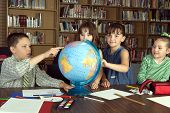 image of school child  - Four Elementary school students study geography in library - JPG