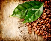Coffee Beans over Wood Background. Beans And Leaf on Wooden Table