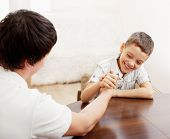 stock photo of wrestling  - Father and son arm wrestling - JPG