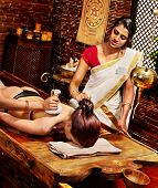 stock photo of panchakarma  - Woman having Ayurveda massage with pouch of rice - JPG