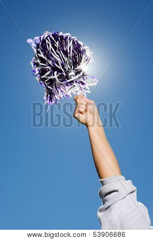Arm of cheerleader holding pom-pom