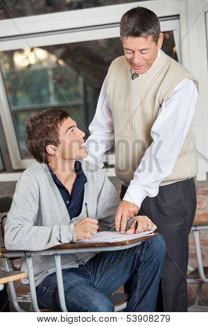 Mature male professor explaining exam to student in classroom