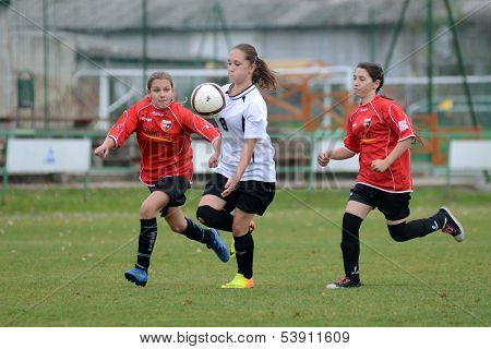 KAPOSVAR, HUNGARY - NOVEMBER 3: Csenge Ujvari (white 8) in action at Hungarian Championship under 15 women soccer game Rakoczi FC (white) vs Pecsi MFC (red) November 3, 2013 in Kaposvar, Hungary.