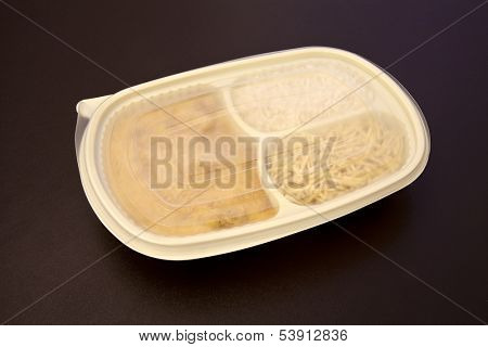 Closed package wit frozen food - Chicken stroganoff with rice and shoestring potatoes - Package on brown leather background.