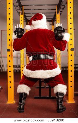 Santa Claus kettlebells training in gym, back view