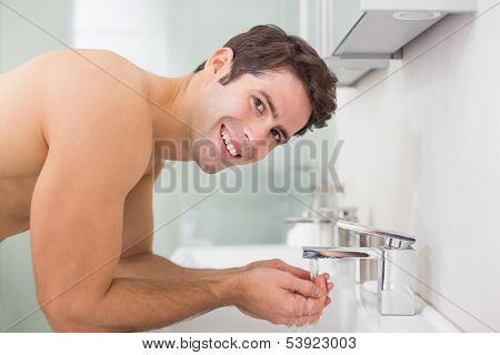 Side view portrait of a shirtless young man washing face in the bathroom