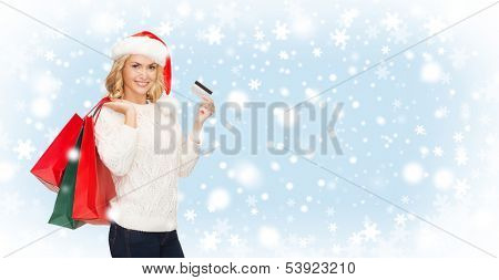 shopping, sale, gifts, christmas, x-mas concept - smiling woman in santa helper hat with shopping bags and credit card