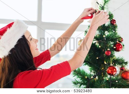 christmas, x-mas, winter, happiness and people concept - smiling woman in santa helper hat decorating a christmas tree