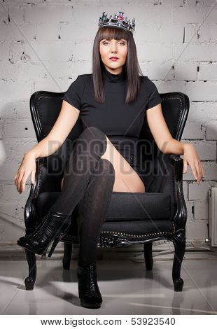 fashion and glamour concept - sexy woman in crown and black dress sitting in chair