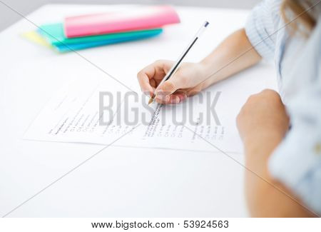 education, children and school concept - little student girl taking test