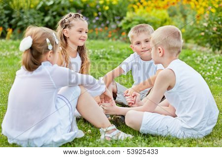 Four children sit on grass at lawn holding hands, one boy yalks, other listen and look at him