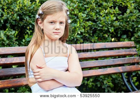 Little girl sits on bench in summer park