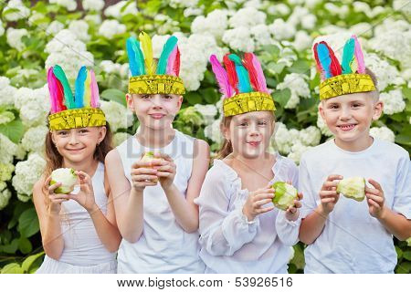 Smiling children in white shirts and with stylized indian feather headdress on heads hold nibbled apples in their hands