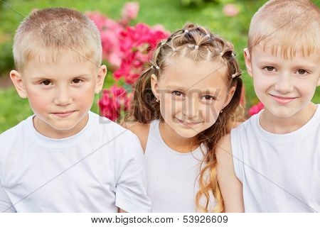 Closeup portrait of three children with flowers at background