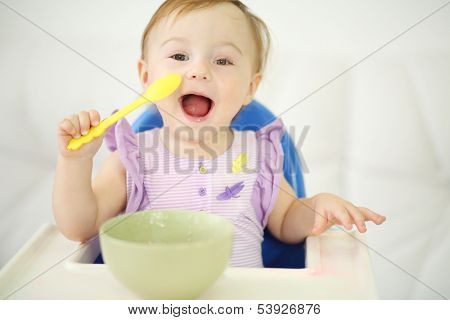 Little happy baby with spoon sits at highchair and eats porridge on plate. Shallow depth of field.