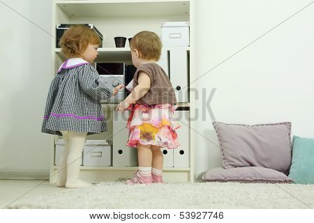Two happy little girls stand near shelves and look at stereo system at home. Shallow depth of field.