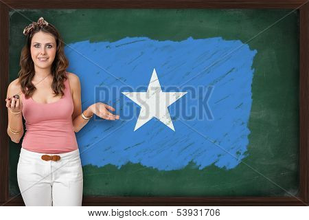 Beautiful And Smiling Woman Showing Flag Of Somalia On Blackboard