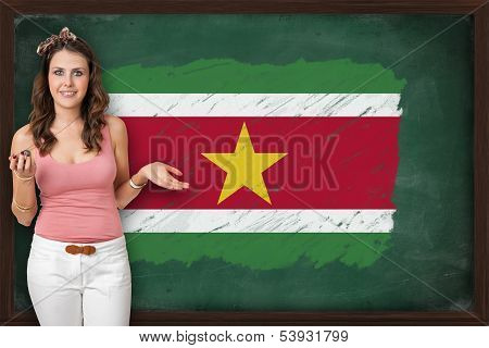 Beautiful And Smiling Woman Showing Flag Of Suriname On Blackboard