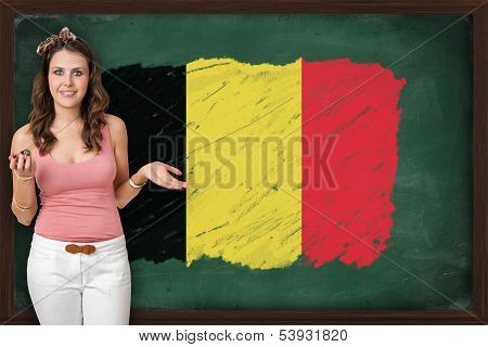 Beautiful And Smiling Woman Showing Flag Of Belgium On Blackboard