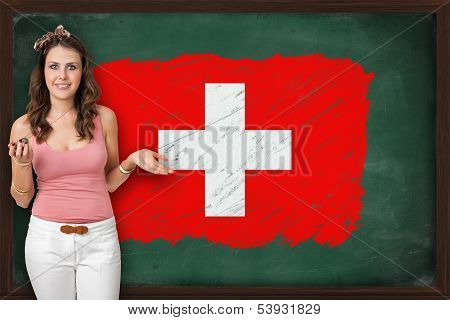 Beautiful And Smiling Woman Showing Flag Of Switzerland On Blackboard