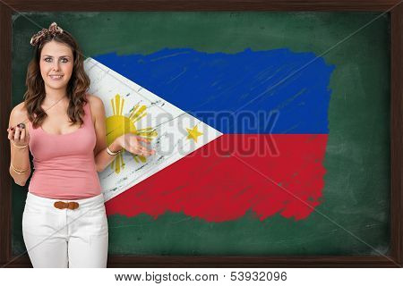 Beautiful And Smiling Woman Showing Flag Of Philippines On Blackboard