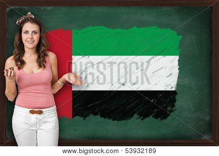 Beautiful And Smiling Woman Showing Flag Of United Arab Emirates On Blackboard