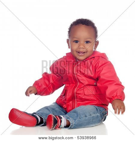 Adorable african baby sitting on the floor with red raincoat isolated on a white background