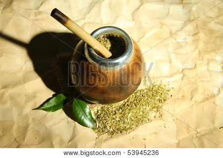 Calabash and bombilla with yerba mate on old paper background