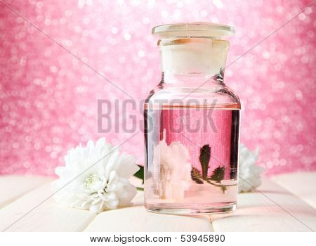 Glass bottle with color essence, on pink background