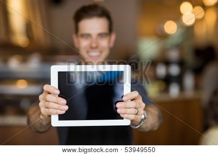 Male cafe owner showing digital tablet in cafeteria