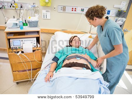 Mid adult female nurse communicating with pregnant patient lying in hospital bed