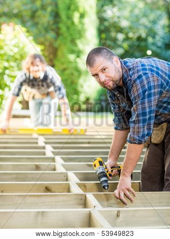 Side view portrait of mid adult carpenter holding drill at construction site
