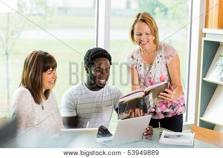 Happy mature librarian assisting university students in library