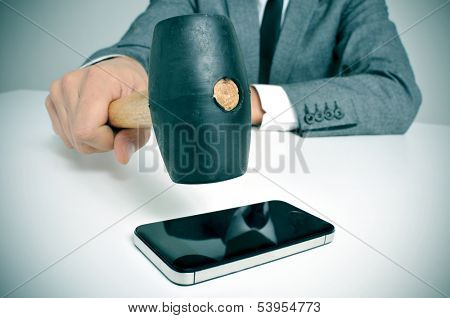 a businessman sitting in a table with a hammer in his hand ready to crash it on a smartphone