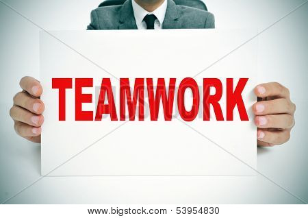 a man wearing a suit sitting in a desk holding a signboard with the word teamwork written in it