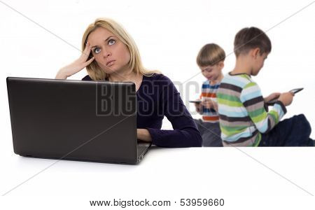 busy mother with laptop and kids with tablet computers