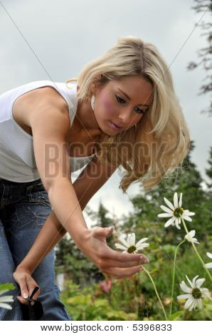 Girl Looking At A Daisy