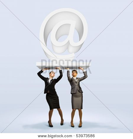 Image of two businesswomen holding at symbol. Partner and cohesion