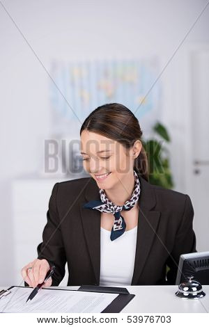 Smiling Receptionist Checking A Clients Booking