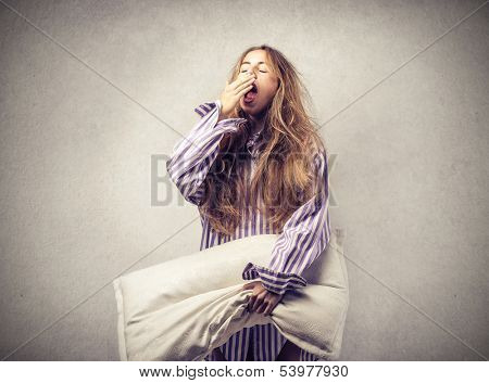 beautiful woman yawning with a pillow in hand