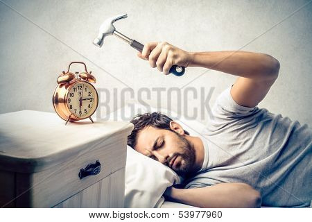 young man tries to break the alarm clock with hammer